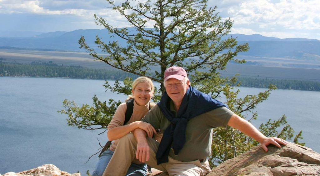 Renee Chambers and husband, Jimmy Milton sitting on rocks with lake behind them.