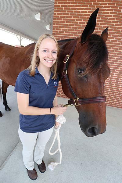 Rachel Pfeifle holds a horse